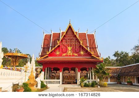 NAN THAILAND - 17 FEBRUARY 2015 - Red gazebo or temple's mondop next to golden pagoda of Phra That Chae Haeng temple in Nan province Thailand.