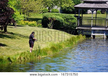 JOLIET, ILLINOIS / UNITED STATES - JUNE 17, 2016: A man enjoys fishing from the side of a small lake in the Wesmere Country Club subdivision of Joliet.