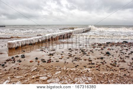 breakwater covered by ice breaking waves on cold gloomy winter day closeup