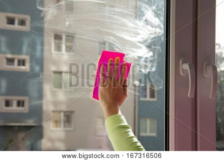female hand washing a window pane inside with red rag closeup