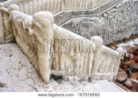 ice covered staircase on the beach on cold gloomy winter day closeup