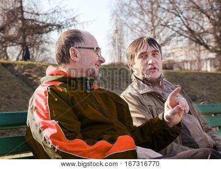 two elderly men talk on a park bench on sunny autumn day