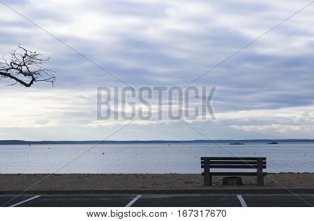 landscape shot of the ocean with a bench silhouetted in the foreground