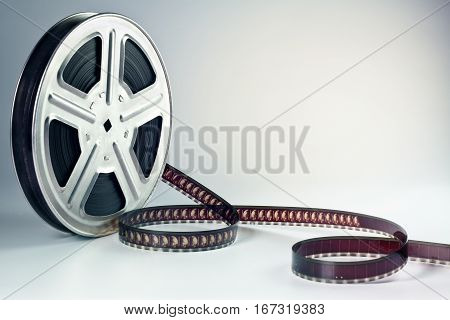 Old motion picture film reel on gray table surface