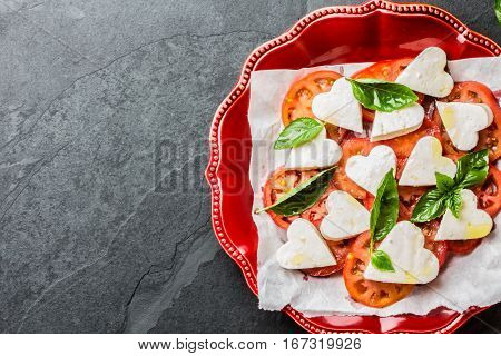 Mediterranean Italian Caprese salad with tomatoes and cheese mozzarella cut as hearts and basil on red plate on slate background. Valentine day menu consept. Top view. Copy space