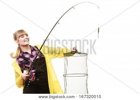 Spinning angling cheerful fisherwoman concept. Happy woman in yellow raincoat holding fishing rod and keepnet having fun.
