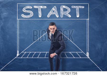Businessman standing in running position on blue blackboard background with chalk drawing of starting gate. Business competition. Goals and success. Business race.