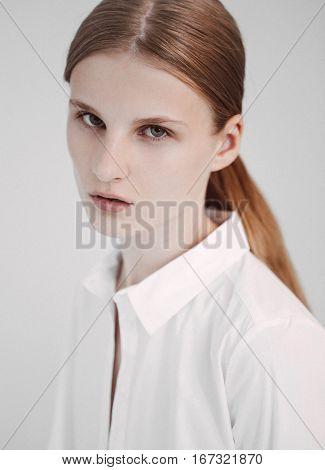 Portrait of red hair fashion model test shooting polaroids on white background