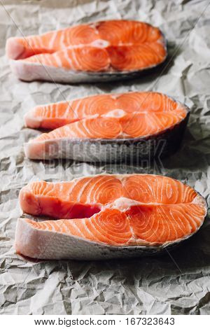 Three Raw Salmon Steaks on Parchment Paper. Vertical.
