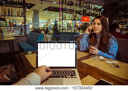first-person view in cafe man working with laptop and looking on young pretty woman