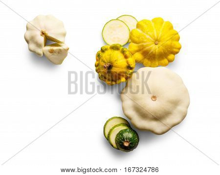 Yellow, white and green zucchini, courgette and round pattipan squashes isolated on white background. Sorts of sliced cucurbit top view