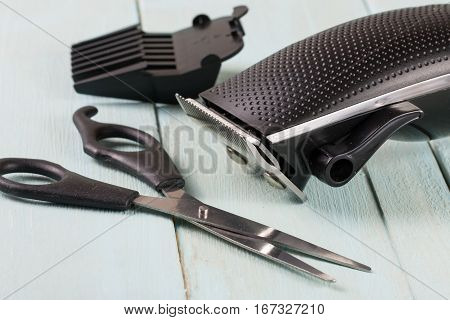 hair trimmer with scissors on the wooden background.