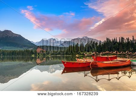 Beautiful high mountains around the incredibly magic lake with red boats and canoe on a spring day.
