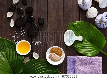 Spa treatment tools and aromatherapy concept background. Zen stones, aroma salt, spices, herbal balls, oil, candle and details of wellness body care and alternative indian medicine, top view