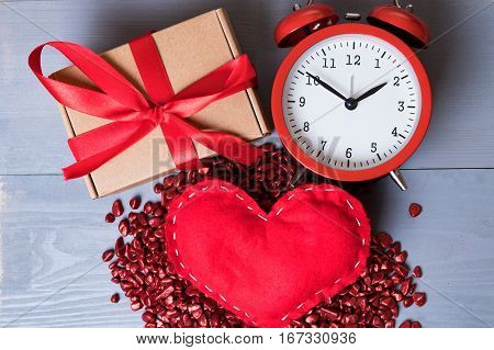 Red homemade heart with present or gift and a vintage clock on Valentine's Day. Time for love or romance abstract concept.