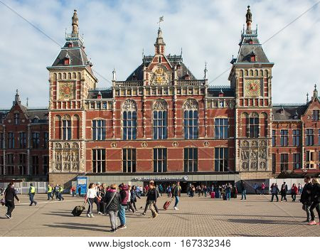 Amsterdam Netherlands - October 3 2016: People infront of the Central Station building in Amsterdam Netherlands on October 3 2016.