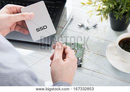 Man is holding modern SSD disk over desk