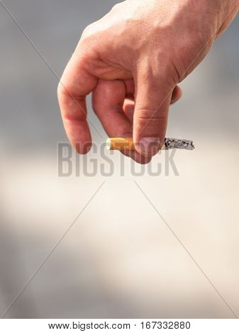 Smoking problem addiction to nicotine concept. Adult man holding and smoking cigarette outside.