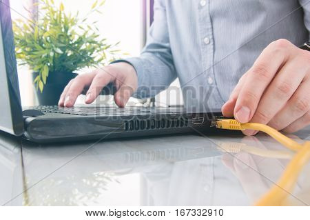 Man is connecting yellow LAN cable into laptop
