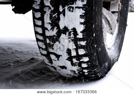 Car or vehicle winter tire in snow on the road