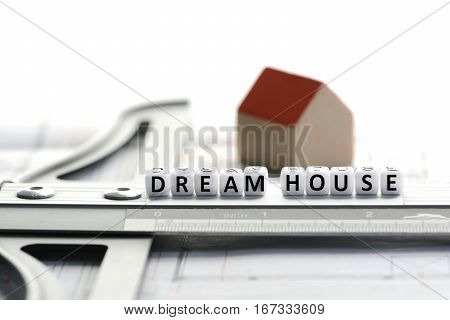 New house project with dream house text on ruler. Architecture plan and small model house on background