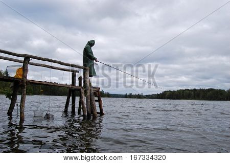 Fisherman standing on the dock in a long raincoat. He is waiting for the fish to bite.