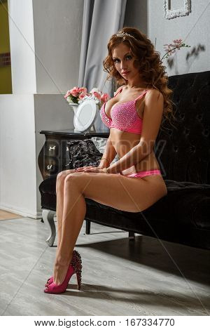 Beautiful sexy brunette in lingerie posing in the interior, hotel, room