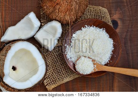 Cracked coconut and grated coconut flakes on wooden plate over dark wooden table overhead view
