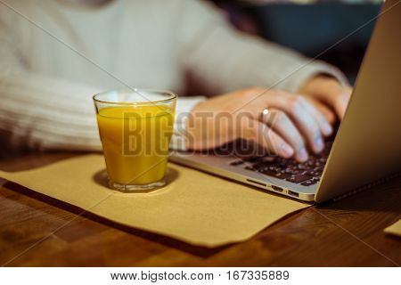 man drinks juse while working on laptop in cafe