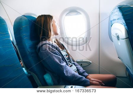 10 years old girl sitting inside airplane and looking at window