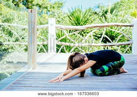 10 years old kid girl doing yoga asana in the nature.