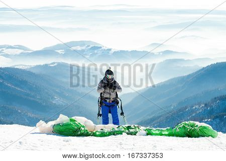 Paraglider in helmet preparing to get launched into air at the peak of a mountain