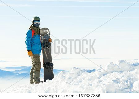 Young Snowboarder In Helmet Standing Next To Snowboard Thrusted Into Snow With Beautiful Scenery Beh