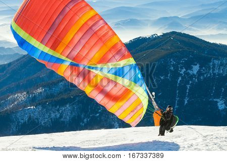 Paraglider Launching Into Air From The Very Top Of A Snowy Mountain Slope
