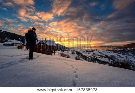 landscape photographer stands on the edge of hillside covered with snow near the village houses in mountainous rural area and looks on winter sunrise