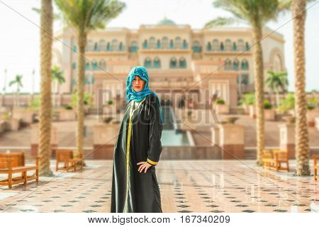 Woman with typical Arab clothes. Luxury vacations and tourism concept. Defocused background at Abu Dhabi, the capital of United Arab Emirates. Holidays, lifestyle and expensive concept.