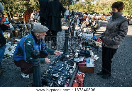 Tbilisi Georgia - October 15 2016: Traders and sellers of flea market on Dry bridge having a lot of vintage watches plates handmade glasses souvenirs and retro staff for the customers.