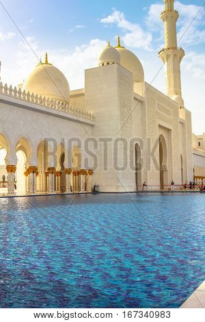 Front and entrance of Sheikh Zayed Grand Mosque in Abu Dhabi, the largest mosque in the UAE. Details of one of the pools along the arcades with columns. Domes and minaret at sunset in the blue sky.