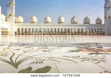 The courtyard with a decoration of Greek and Italian white marble of Sheikh Zayed Grand Mosque in Abu Dhabi, United Arab Emirates, the third largest mosque in the world.