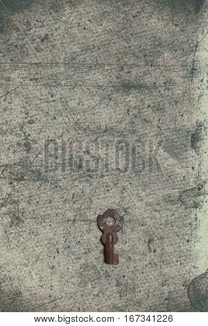 Old key on the old textured paper with natural patterns. Distressed vintage key with texture overlay