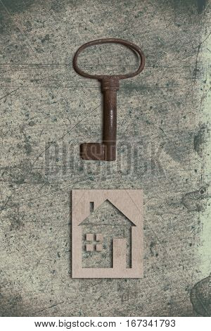 model of cardboard house with key on old textured paper background. House building, loan, real estate or buying a new home concept.