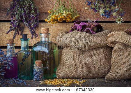 Healing Herbs In Hessian Bags, Bunches Of Medicinal Herbs And Bottles Of Tincture Or Oil, Herbal Med