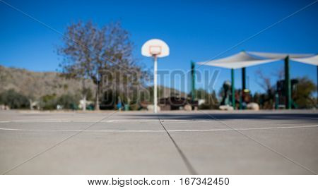 Basketball court, hoop, and backboard--horizontal view with a park and sky background.