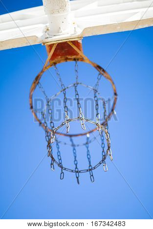 Basketball hoop and backboard--vertical view from behind with a sky background.