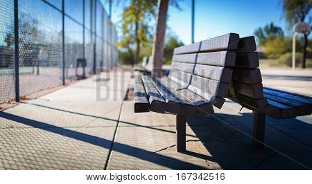 Play park and tennis court park bench. Depth-of-field view.