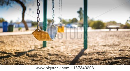 Play park kid's swings in a row. Close up/depth of field view of first swing.