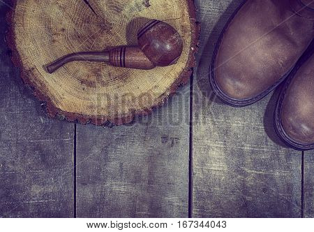 Wooden smoking pipe tobacco with a pair of leather boots old worn surface top view