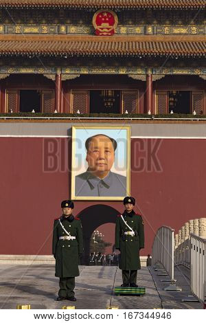 Beijing, China - January 3, 2017: Guards outside the Forbidden City at Tian'anmen, the gate of heavenly peace stand below a painting of Mao.