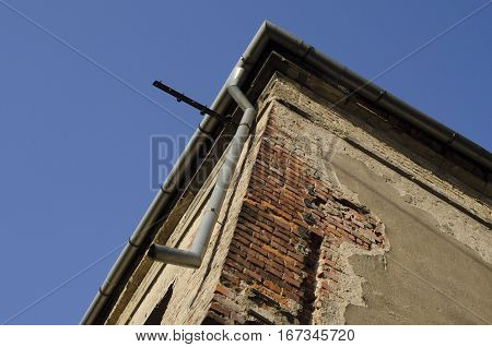 Corner of old unused house with blue sky in background