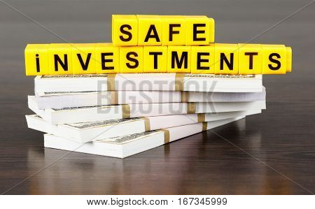 Safe investments concept word made by letter blocks. Stack of money american hundred dollar bills
